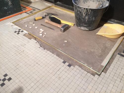 En pleine restauration d'une fosse à tapis détériorée à Neuilly sur Seine, Ile-de-France. Reprise des bords en maçonnerie, pose d'un nouveau cadre en laiton, et réparation de la mosaïque de grès cérame